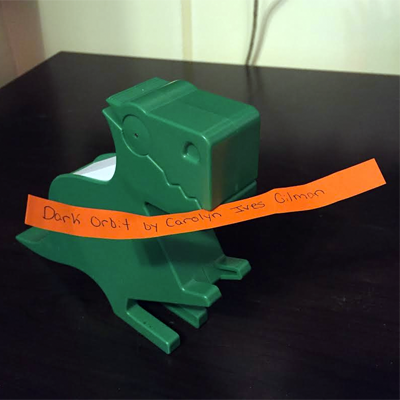 Green dinosaur holding orange slip of paper reading Dark Orbit by Carolyn Ives Gilman