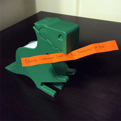Green dinosaur holding orange slip of paper reading Ghost Summer: Stories by Tananarive Due