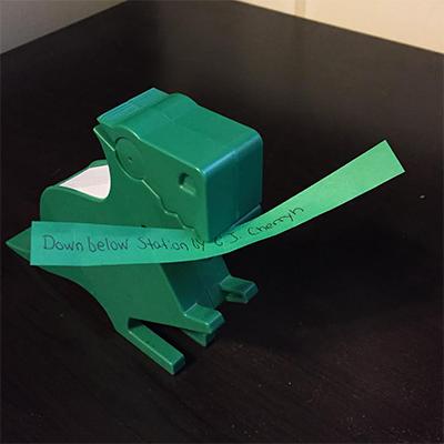 Green dinosaur holding orange slip of paper reading Downbelow Station by C.J. Cherryh