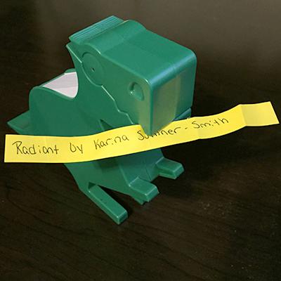 Green dinosaur holding orange slip of paper reading Radiant by Karina Sumner-Smith