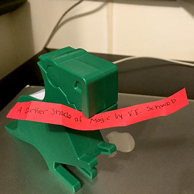 Green dinosaur holding red slip of paper reading A Darker Shade of Magic by V.E. Schwab