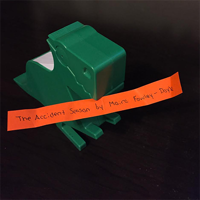 Green dinosaur holding orange slip of paper reading The Accident Season by Moïra Fowley-Doyle